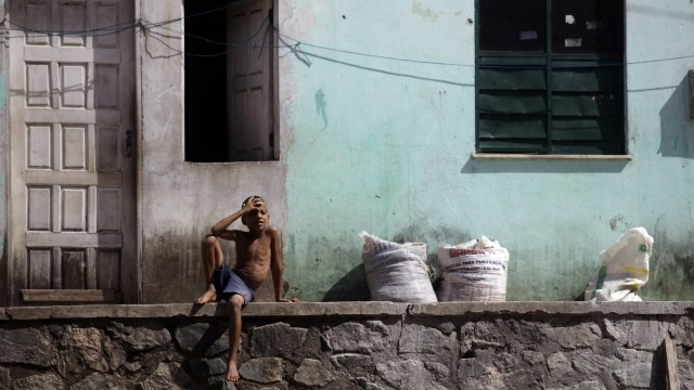 Child sits in front of his house in Salvador, northeast Brazil