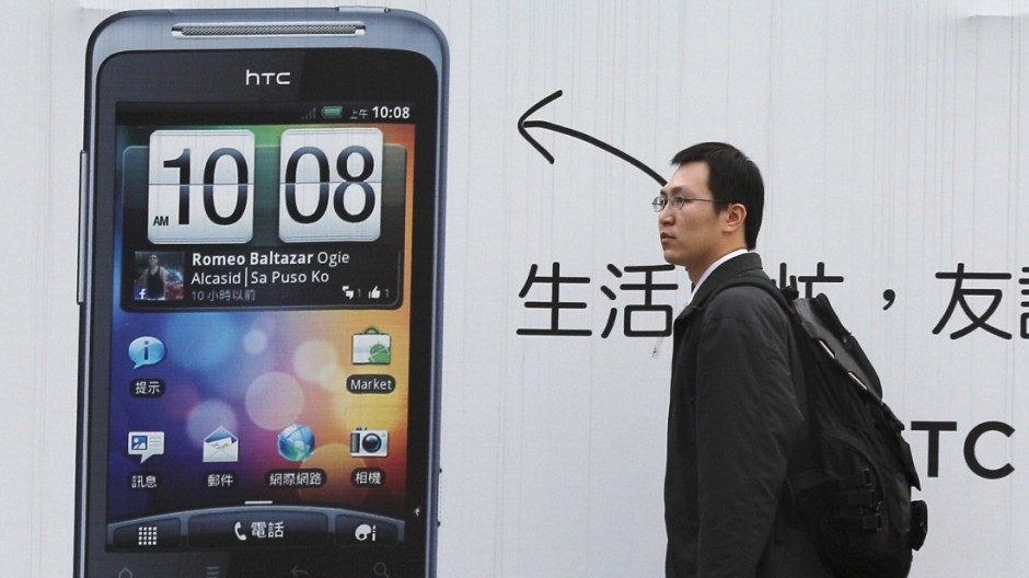 A man walks past a HTC advertisement in Taipei