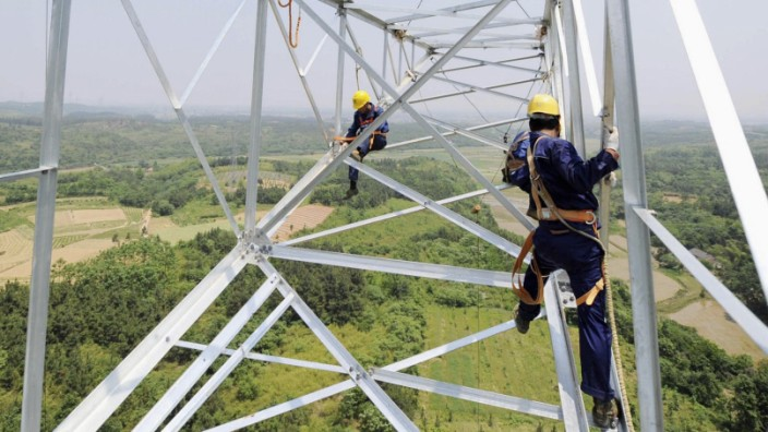 Workers install a high voltage electricity pylon in Xuancheng