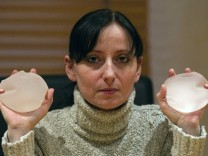 Alexandra Blachere displays silicone gel breast implants during an interview in Paris