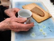 Alte Hände mit Teetasse und Brotscheibe, 2010