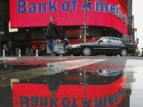 File photo of a woman reflected in a puddle as she passes a Bank of America branch in New York's Times Square