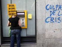 A protester carrying a banner withdraws money from an ATM machine of a bank during a demonstration in Madrid