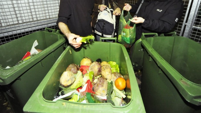 Containern - Junge Leute suchen nach Lebensmitteln in Mülltonnen