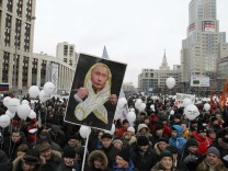 Demonstrators gather holding placards and balloons during a protest against recent parliamentary election results in Moscow