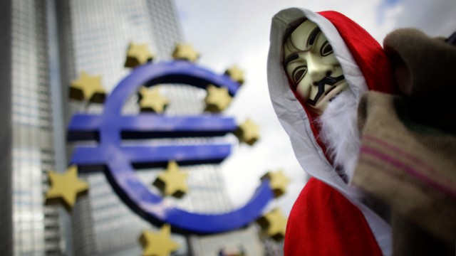 A protester of the occupy movement wears a Santa Claus costume as he walks through the occupy camp in Frankfurt