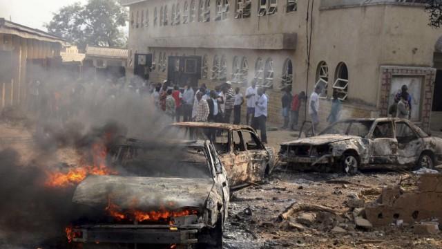 A car burns at the scene of a bomb explosion at St. Theresa Catholic Church at Madalla