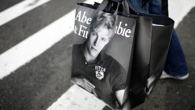 A man holds shopping bags while waiting to cross a street in New York