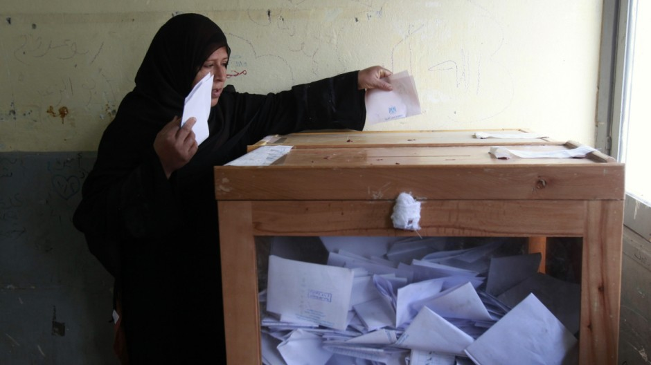 A woman casts her vote in a school used as a voting center in Al-Arish city