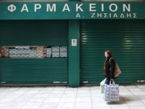 A woman passes in front of a closed pharmacy store during a 48-hour pharmacists strike in Athens