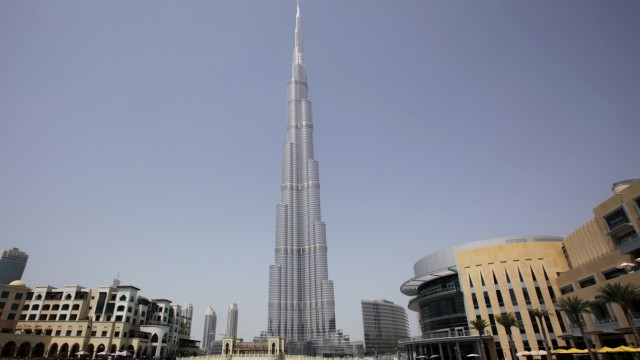 Workers move on a boat in an artificial lake at Dubai Mall in front of Burj Khalifa in Dubai