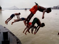 INDIAN CHILDREN JUMP INTO THE RIVER HOOGHLY IN AN EFFORT TO GET SOME RESPITE FROM THE HEAT IN CALCUTTA