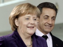 French President Sarkozy and German Chancellor Merkel arrive for news conference in Berlin