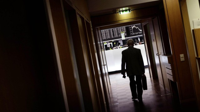 A share trader walks out of Frankfurt's stock exchange