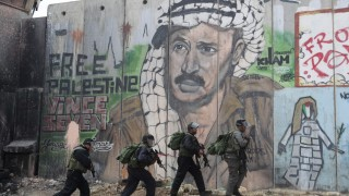 Israeli police and border officers walk in front of a mural depicting Arafat at Qalandiya checkpoint