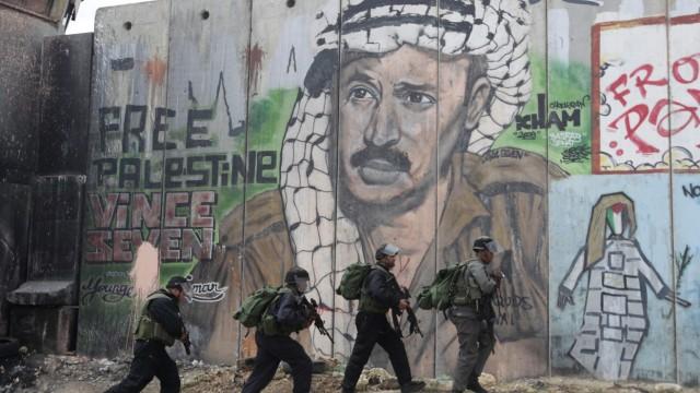 Israeli police and border officers walk in front of a mural depicting Arafat at Qalandiya checkpoint
