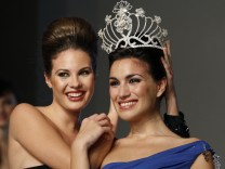 Ana Araceli Jimenez is crowned Miss Sevilla by last year's winner Jessica Bueno in Seville