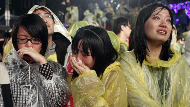 Supporters of Democratic Progressive Party Chairperson and presidential candidate Tsai Ing-wen cry while watching Tsai on the podium at their campaign headquarters in Taipei