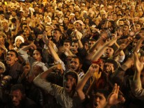 Anti-government protesters shout slogans as they react to departure of Yemen's outgoing President Saleh in Sanaa