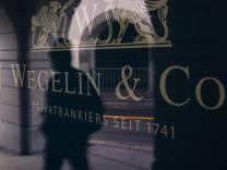 A man is reflected in the window of Swiss Wegelin bank headquarters building in St. Gallen