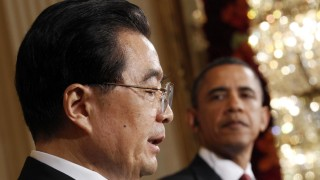 U.S. President Barack Obama looks on as Chinese President Hu Jintao speaks during a joint news conference in the East Room of the White House in Washington