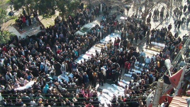 Residents attend a burial ceremony for what activists say are victims of shelling by the Syrian army, in the Khalidiya neighbourhood in Homs