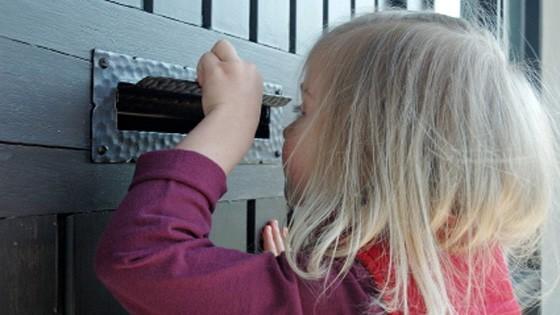 Mädchen schaut in Briefkasten