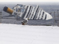 A seagull stands on the roof of a house in front of the capsized Costa Concordia cruise ship at Giglio island