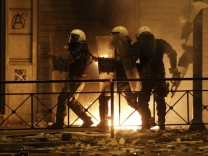 Riot police protect themselves behind their shields during violent protests in central Athens