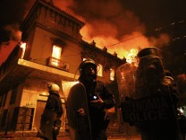 Policemen stand in front of a burning building following violent anti-austerity protests in Athens