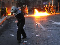 A protester runs away from police in Athens during riots