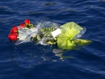 Flowers thrown by family members of missing victims from the Costa Concordia cruise ship which ran aground off the west coast of Italy, float near the Costa Concordia at Giglio island