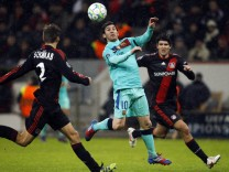 Bayer Leverkusen's Schwaab and Corluka challenge FC Barcelona's Messi during their Champions League soccer match in Leverkusen