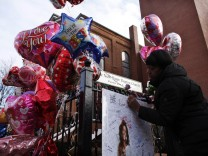 A woman writes a message on a memorial for pop singer Whitney Houston, outside of New Hope Baptist Church in Newark