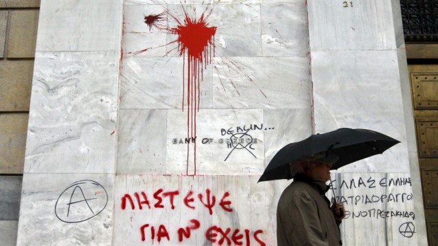 A man passes the defaced facade of the Bankof Greece after a night of violence following the Greek parliament approval of a deeply unpopular austerity bill in Athens