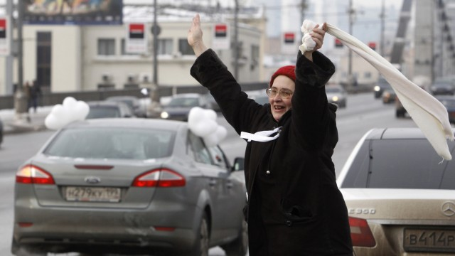 A woman greets participants of a car rally held to ask for a fair election, in Moscow