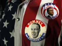 A supporter wears campaign buttons from Republican presidential candidate and former Massachusetts Governor Mitt Romney's 2012 campaign, and from the 1968 campaign of George Romney, Mitt Romney's father, in Tampa