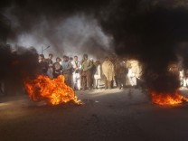 Afghan men stand near tyres, set on fire by the protesters, during a demonstration in Jalalabad province