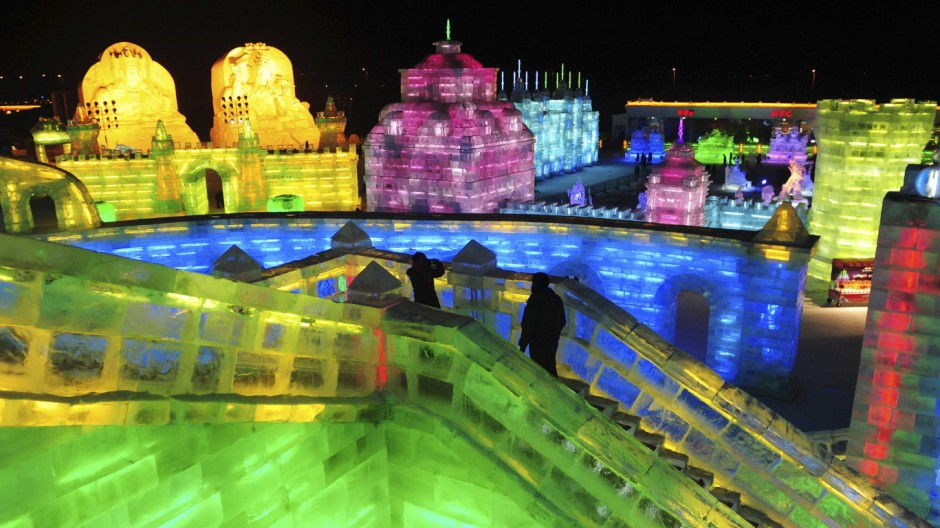 Tourists visit ice sculptures on the night before the opening ceremony of the 13th Harbin Ice and Snow World in Harbin