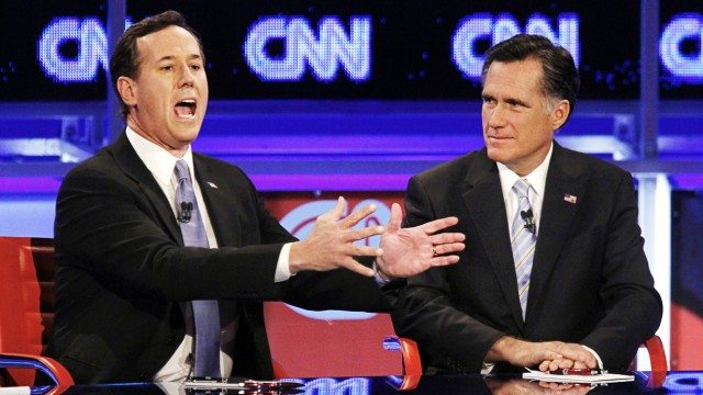 U.S. Republican presidential candidate Santorum speaks as Romney looks on during the Republican presidential candidates debate in Mesa