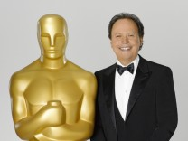Comedian Billy Crystal, host for the 84th Academy Awards, poses in this undated publicity photograph with a large Oscar statuette