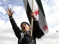 A boy takes part in a demonstration against Syria's President Bashar Al-Assad in front of the Syrian embassy in Amman