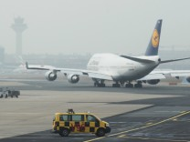 Airport apron controller vehicle is pictured next to Lufthansa aircraft on runway at Frankfurt's airport