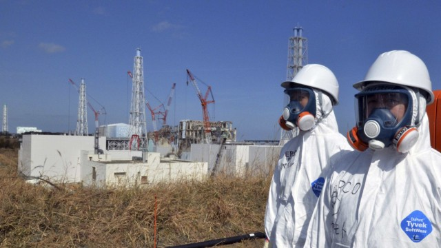 TEPCO's workers stand near the crippled TEPCO's Fukushima Daiichi nuclear power plant ractor buildings in Fukushima