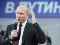 Vladimir Putin attends a meeting with his supporters