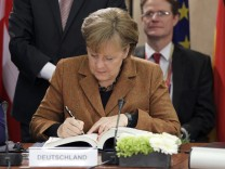 Germany's Chancellor Merkel signs a fiscal compact enshrining common debt rules among the 17 members of the euro zone during a European Union leaders summit in Brussels