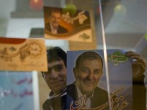 A campaign volunteer shows a campaign poster at his campaign headquarters in Karaj
