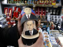 A seller demonstrates Matryoshka dolls bearing the faces of Putin and Medvedev in St. Petersburg