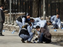 Forensic police officers inspect the scene of an explosion in Ankara