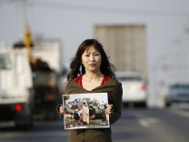 Yuko Sugimoto stands on a road in Ishinomaki